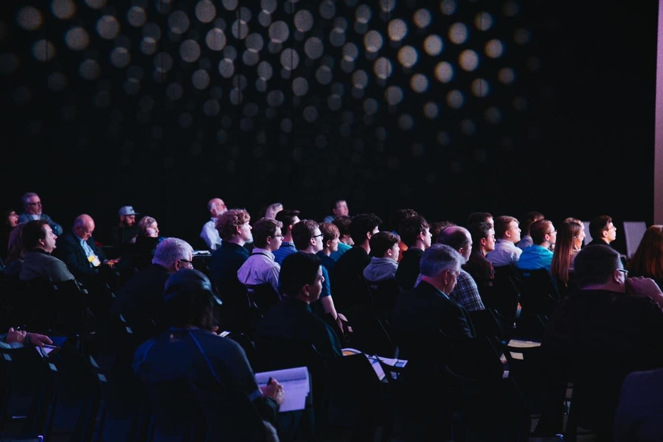 Public qui assiste à une présentation dans une salle de conférence